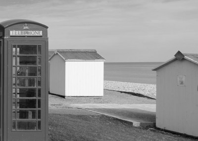 Old fashioned red telephone box and beach huts at Budleigh Salterton