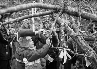 Mother and child tying a ribbon to the Wassail tree