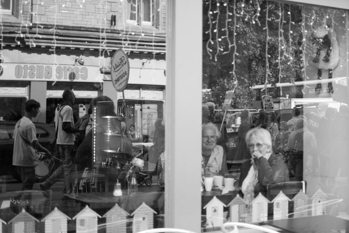 Reflection of the anti-austerity march in a Bristol window
